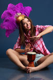 Singing girl in hat with feathers sits on floor and beats drum. Singing girl in pink shirt in hat with feathers sits on floor and beats drum stock image
