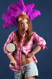 Singing girl in hat with feathers with small drum Stock Photo