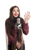 Singing girl with microphone on stand. Singing girl isolated on white with microphone on stand Royalty Free Stock Image