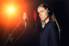 Singing girl sing to the professional microphone in the record studio. Process of create a new hit song by young singer royalty free stock photo