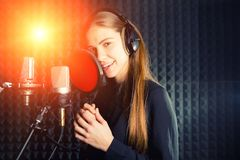 Singing girl sing to the professional microphone in the record studio. Process of create a new hit song by young singer royalty free stock image