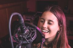 Singing girl singing with a microphone royalty free stock images