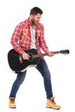 Singing guitarist. Guitarist in red lumberjack shirt standing with legs apart and play the black acoustic guitar. Full length studio shot isolated on white Royalty Free Stock Photography