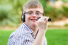Singing handicapped boy. Close up portrait of young handicapped man singing with microphone outdoors royalty free stock image