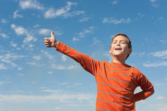 Singing happy boy in front of the sky. A happy kid is holding his thumb up and singing in front of the blue sky stock photography