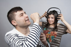 Singing Karaoke. Couple having fun: men singing karaoke and the girl hits her ears Royalty Free Stock Image