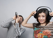 Singing Karaoke. Couple having fun: men singing karaoke and the girl hits her ears with gray background Royalty Free Stock Images
