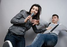 Singing Karaoke. Couple having fun: girl singing karaoke and the push the man, they are fighting for microphone Royalty Free Stock Images