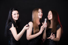 Singing karaoke. Three beautiful girls in karaoke, focus on brunette girl with remote control trying to switch off song, her friends having fun, singing with Stock Photography