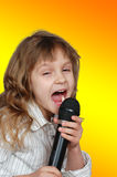 Singing kid with a microphone Stock Image