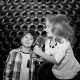Singing little children with a microphone on a rack against a bl Stock Photography