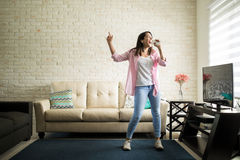 Singing in the living room. Independent woman singing karaoke alone in her apartment and having fun in the living room Royalty Free Stock Image