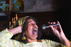 Singing for the Lord. Closeup of a mature gospel or soul singer in a dark church Royalty Free Stock Image