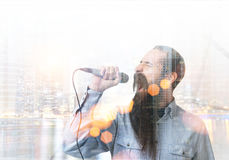 Singing man with a beard in a city stock images