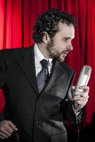 Singing man with black suit and microphone on background Royalty Free Stock Images