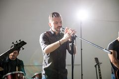 Singing a melodious song in concert. Hispanic male lead singer singing a melodious song live in a music concert Stock Photography