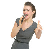 Singing in microphone woman showing thumbs up Royalty Free Stock Image