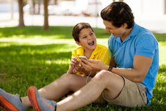 Singing with my dad. Cute young boy having fun and singing a song with his dad while relaxing in a park Royalty Free Stock Photos
