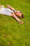 Singing is my joy. Child singing with microphone and lying on grass - outdoor lifestyle Stock Image