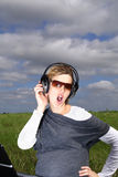 Singing outdoors. A woman listening to her favourite song and singing along in the fields Royalty Free Stock Photography