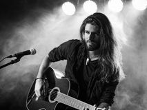 Singing and playing acoustic guitar on stage. Photo of a young man with long hair and a beard playing an acoustic guitar on stage with lights and concert Royalty Free Stock Photos