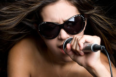 Singing Rockstar. Beautiful brunette karaoke rockstar singing Stock Photo
