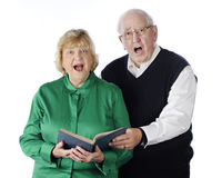 Singing Senior Couple. A senior adult couple singing praises together from a hymnal.  On a white background Royalty Free Stock Images