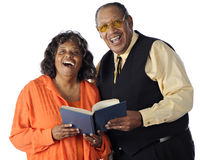 Singing Senior Couple. A senior African American couple sing together from a songbook. On a white background royalty free stock photos