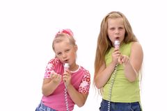 The singing sisters/friends. Two sisters or friends singing and pointing to you Stock Images