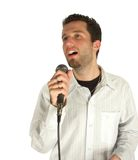 Singing softly. Attractive young man singing with a microphone isolated over white background Stock Image