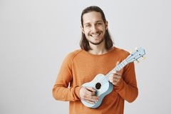 Singing Song During Travel In Train. Portrait Of Friendly Handsome Male In Orange Sweater Holding Ukulele, Playing Royalty Free Stock Photography