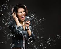 Singing song rock musician with mic and earphones Stock Image