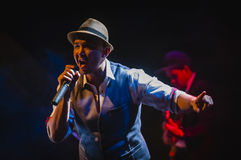 Singing on stage in dark studio Royalty Free Stock Photography