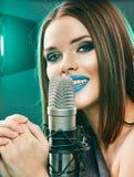 Singing star. Woman singer portrait. Sound studio stock photo