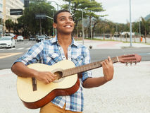 Singing street musician with guitar in the city. Street musician with playing guitar outdoor in the city Stock Images