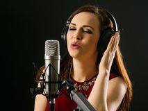 Singing into a studio microphone Stock Images