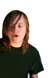 Singing Teen Boy. 14 year old teenage boy with long hair and closed eyes singing, isolated on a white background stock image