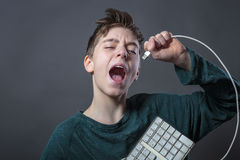 Singing teenage boy with computer keyboard. And gray background for fast isolating royalty free stock photos