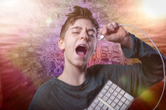 Singing teenage boy with computer keyboard. And spacy background Stock Image