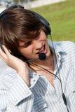 Singing teenage boy in headphones. Against the nature stock photos