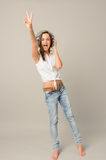 Singing teenage girl headphones show victory sign. Full length on gray Royalty Free Stock Photo