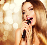 Singing teenage girl with microphone. Karaoke party Royalty Free Stock Image