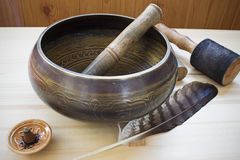 Singing Tibetan bowl. With mallets, feather and aroma cone on a wooden table. Asian traditional theme Royalty Free Stock Photography