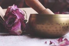Singing Tibetan yoga bowls. Purple flower and little Book royalty free stock image