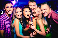 Singing together. Portrait of happy girls and guys singing in microphone in the karaoke bar Royalty Free Stock Photography