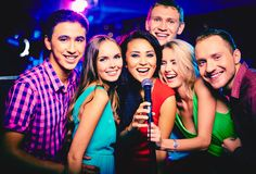 Singing together. Portrait of happy girls and guys singing in microphone in the karaoke bar Stock Photography