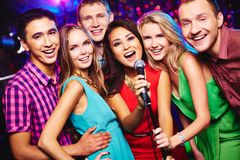 Singing together. Portrait of happy girls and guys singing in microphone in the karaoke bar Royalty Free Stock Image