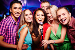 Singing together. Portrait of happy girls and guys singing in microphone in the karaoke bar Stock Image