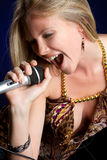 Singing Woman. Singing blond woman holding microphone Stock Photography