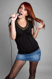 Singing Woman. Beautiful redhead woman singing karaoke Stock Photos